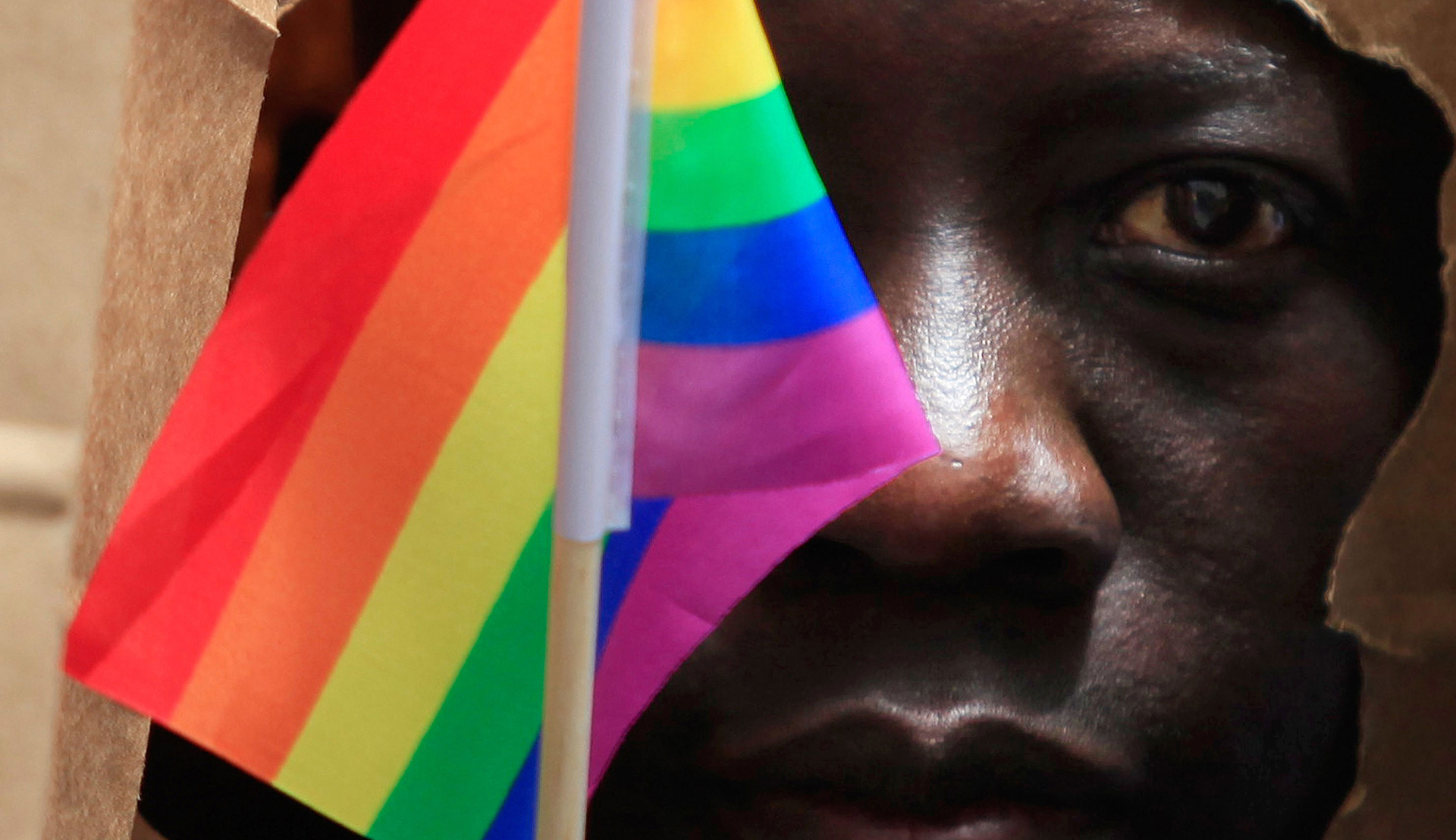 Rutgers Global - LGBT Rights Under Fire in Uganda: The Influence of U.S. Fundamentalism and the Repression of a Movement, close up of a man waving a small rainbow flag