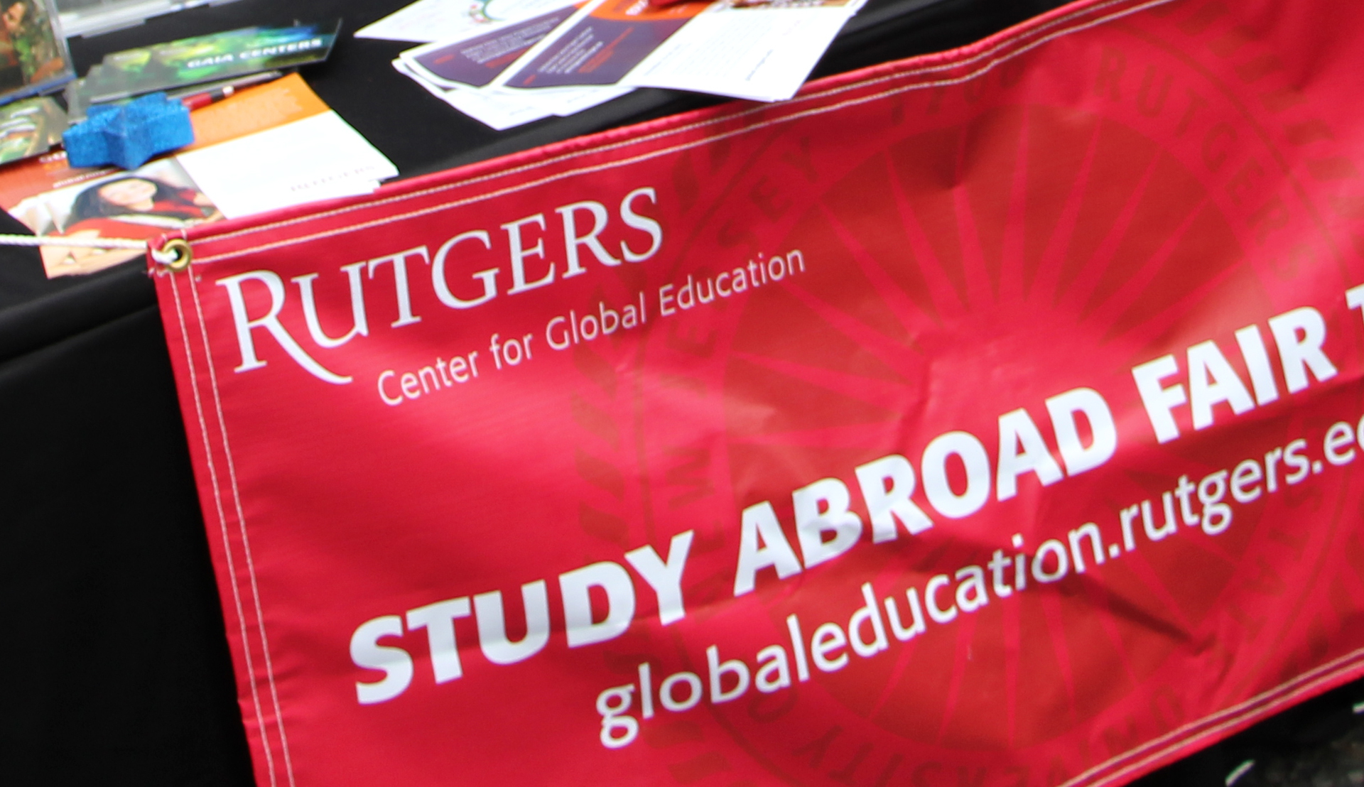 Rutgers Global - Spring 2016 Study Abroad Fair, study abroad fair today banner on exhibit table with assortment of Rutgers Global flyers