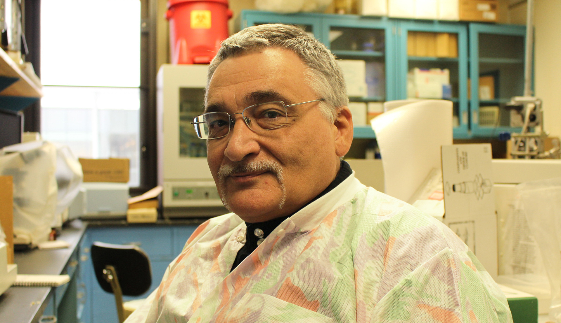 Rutgers Global - Probiotics Research Spans the Globe, Michael Chikindas poses for a seated photo in SEBS laboratory wearing lab coat