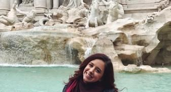 Julia is standing in front of the Trevi Fountain.