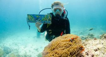 Katya is scuba diving at the Great Barrier Reed. There is an anemone and clown fish in front of her and she holds a post card.