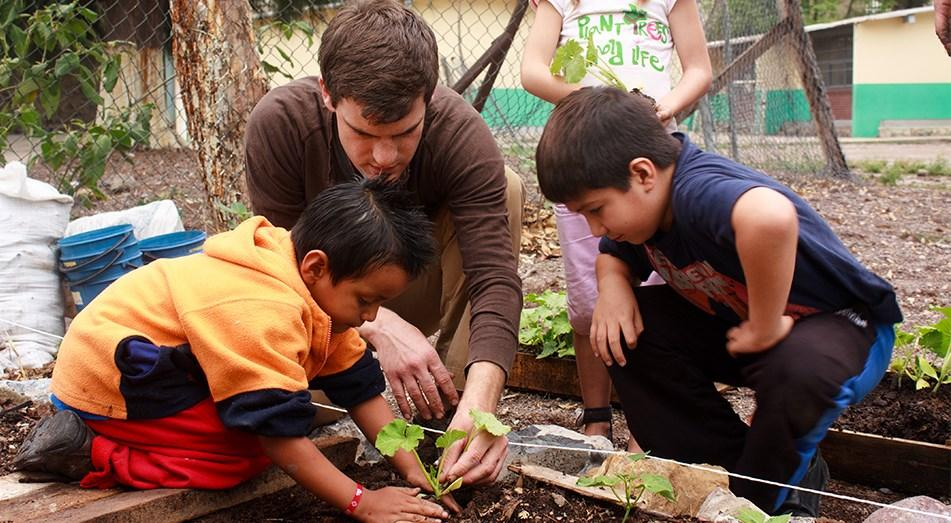Rutgers Global – Peace Corps, volunteer plants tree with local children