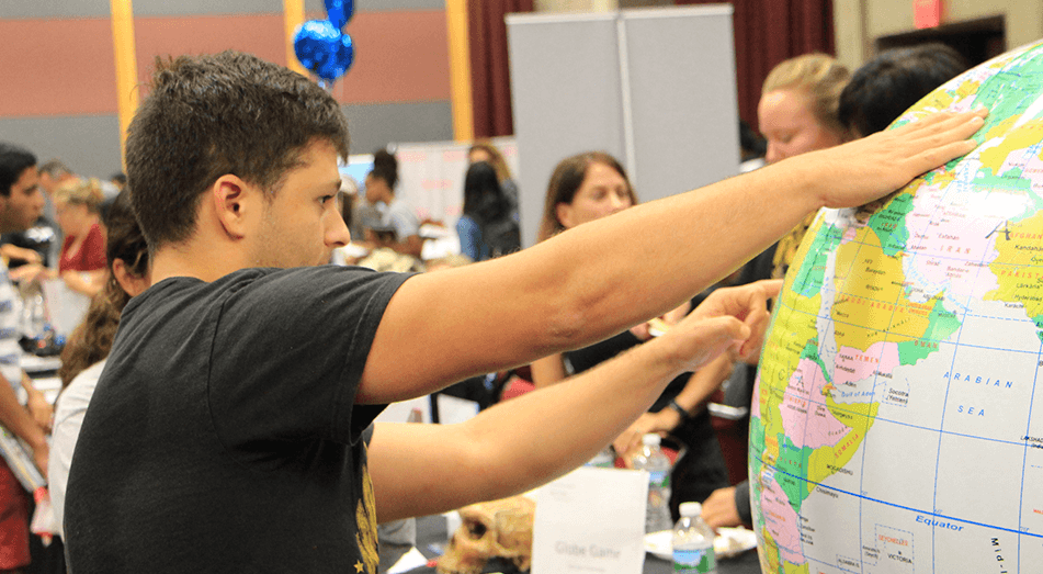 Rutgers Global - Spring 2018 Study Abroad Fair, student points to a country on a large inflatable globe; the background shows crowd of students and exhibitors