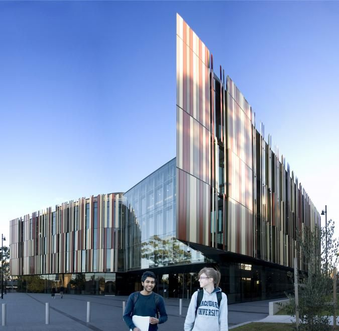 Two Macquarie students walk and laugh. Behind them is a large building with many glass panels of different reds and taupe.
