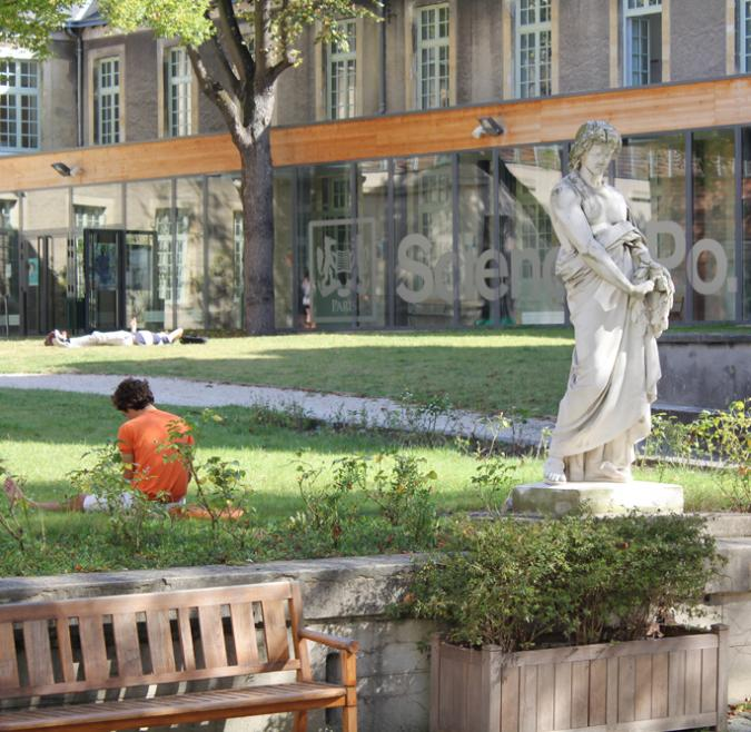 A marble statue sits before a Reims campus quad. Students are seen studying and lounging in the grass, and the Sciences Po logo is in the background on a window of the building