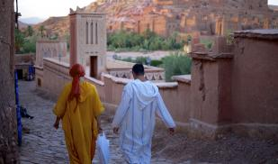 Two people are seen from behind, walking down a hill. They are wearing robes, one bright yellow with their head wrapped in a red scarf, the other in blue and white stripes. In front of a mountain in the background are many terra cotta structures.