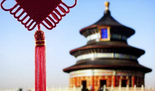 In the foreground, a red tassle hangs in front of the blue sky. In the background is a traditional Chinese temple.
