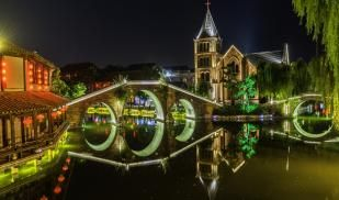 Trees and bridges are lit up with neon decorations. Their image is reflected in a river.