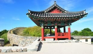 A tradition Korean structure with red and green details sits on a hill on a sunny day