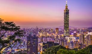 From a hilltop, the Taipei skyline is viewed. There are many skyscrapers, but one is towering over the rest. It is sunset, so all is illuminated orange and purple