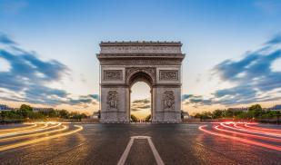 The Arc de Triomphe is in the center with the sun setting behind it and the headlights of cars stream by
