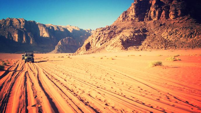 Two SUV's drive in the red sand with mountains behind them