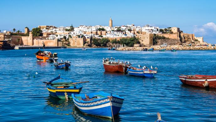 Colorful boats sit on the blue ocean water with a seaside town in the background