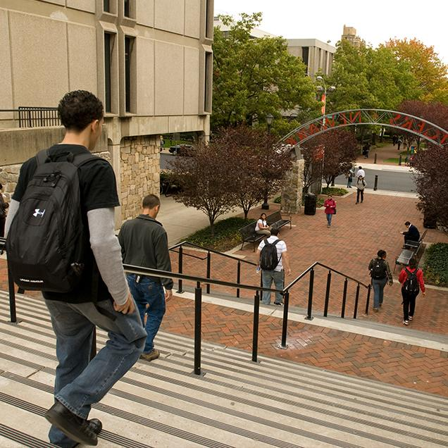 Rutgers Global – International Exchange Students, students wearing backpacks descend steps at Rutgers–Newark campus