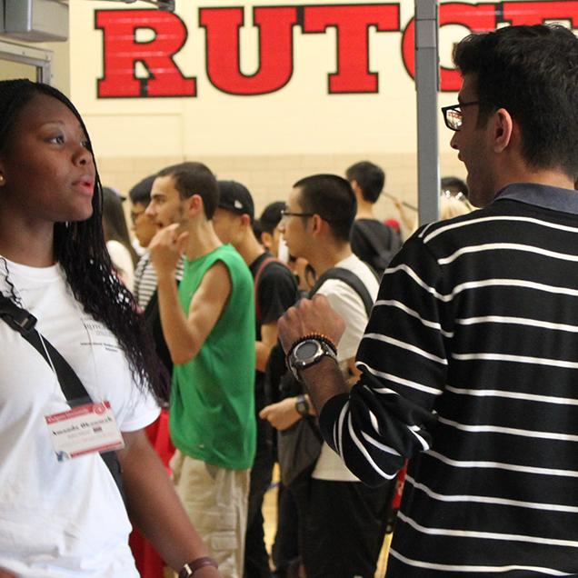 Rutgers Global – FAQs, student asks another student a question at a well-attended Rutgers event