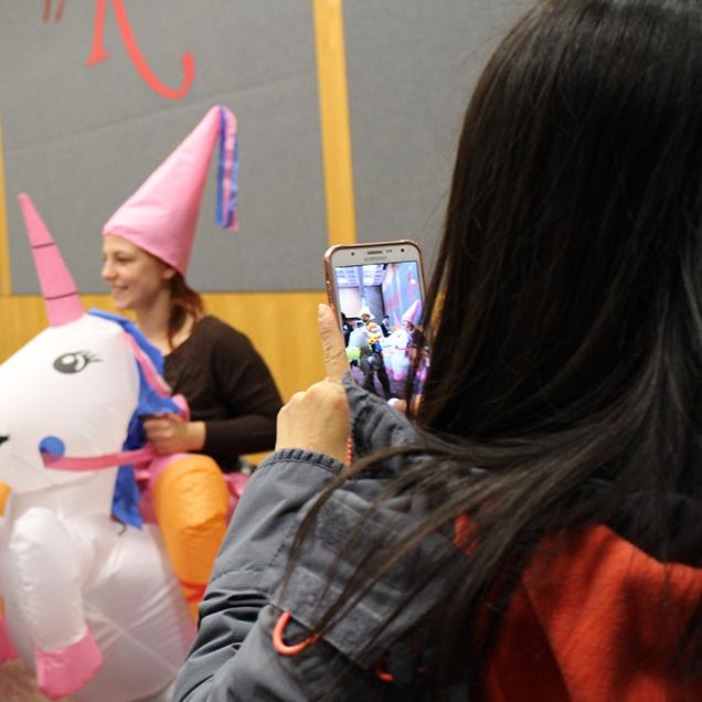 Rutgers Global - Events for the Whole Family, a scholar takes a picture of a colleague and her family at the annual Rutgers global ghouls gala Halloween party
