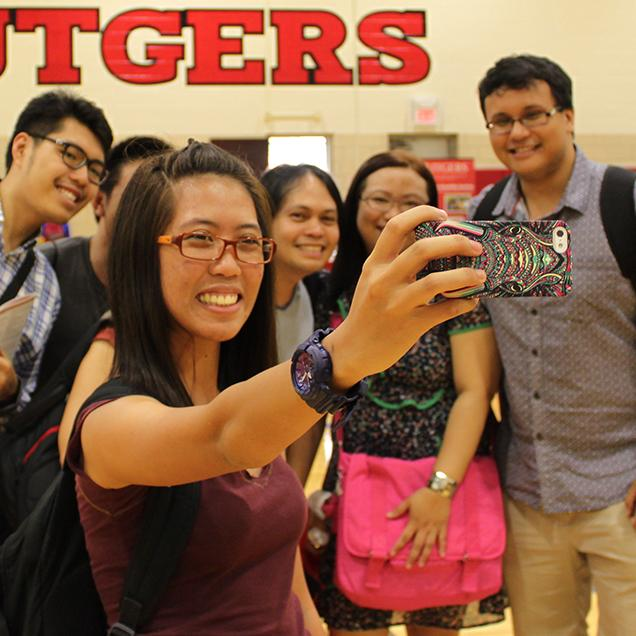 Rutgers Global – Tailored Group or Certificate Programs, six students pose for a group selfie in Rutgers gym, girl holds a multicolored phone