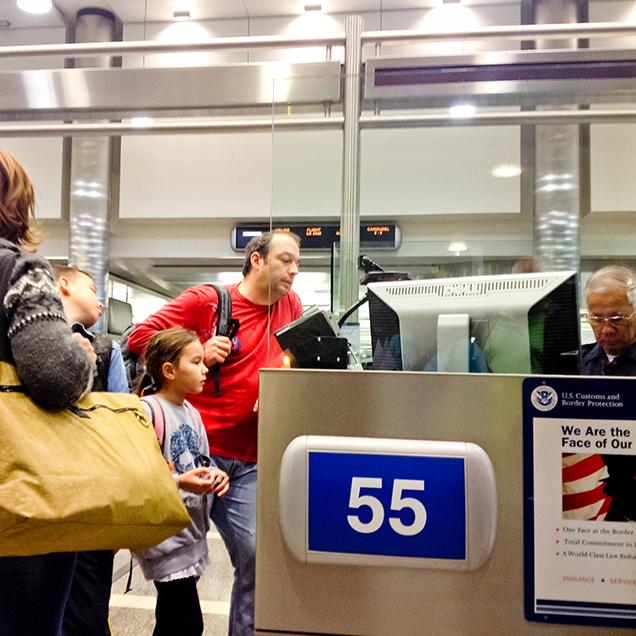 Rutgers Global - Requesting J-2 Documents for Dependents of Scholars and Research Students, a man, his wide, and young daughter speak with an older customs agent at an airport before entering the U.S.