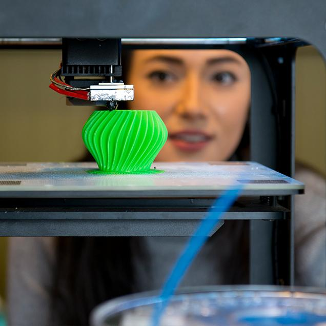 Rutgers Global – Summer Session and Hybrid Language Program, student watches 3-D printer produce a green votive
