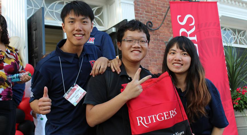 Rutgers Global – About the Center for Global Services, three student volunteers pose in front of the College Age Gym