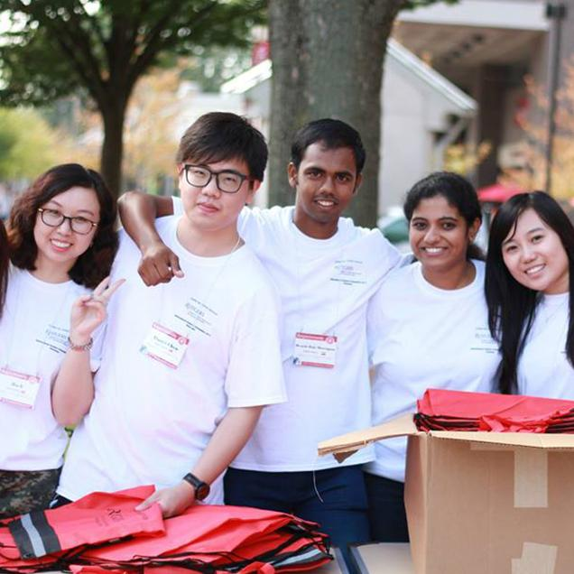 Rutgers Global – International Student and Scholar Services, five students in white tee shirts smile for a photo on College Avenue, outdoors