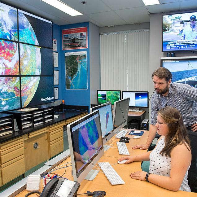 Rutgers Global - UN SDG Faculty Research, two researchers examine a monitor in the RUCOOL laboratory in front of a large Google Earth display