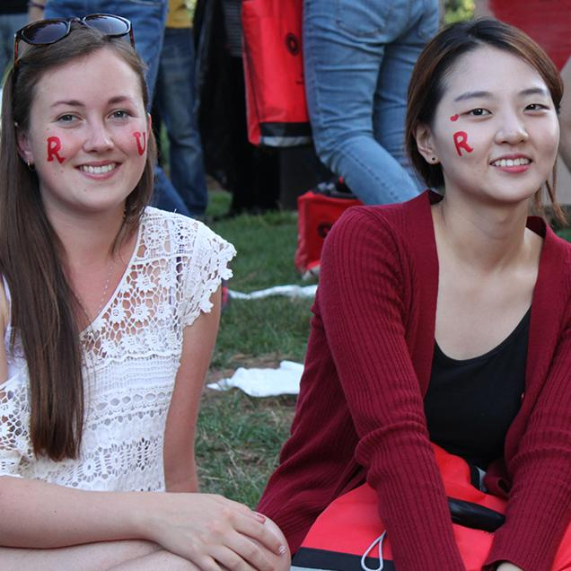 "Rutgers Global – IFP, two students enjoy an outdoor picnic with ""R"" spirit mark face paint on their faces"