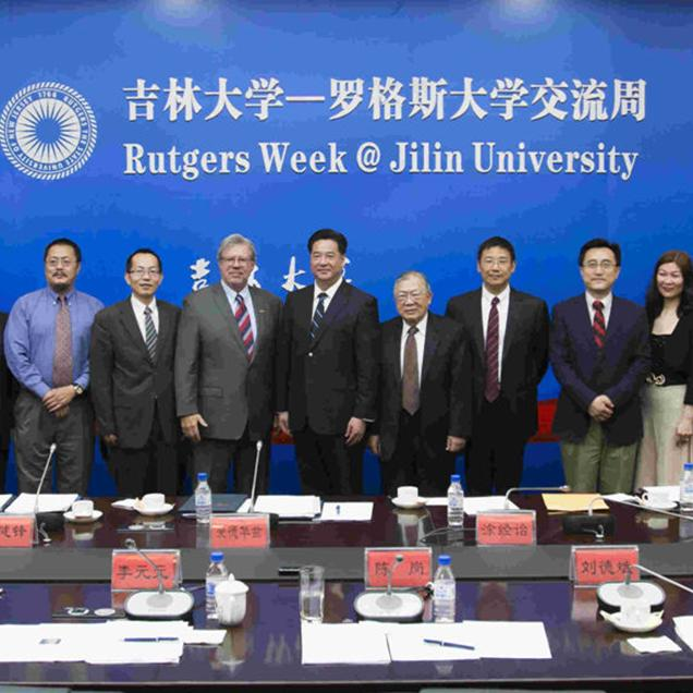Rutgers Global – Rutgers Week at Jilin University, delegation and partners pose for a photo in front of a large blue backdrop with Rutgers' seal and name on it