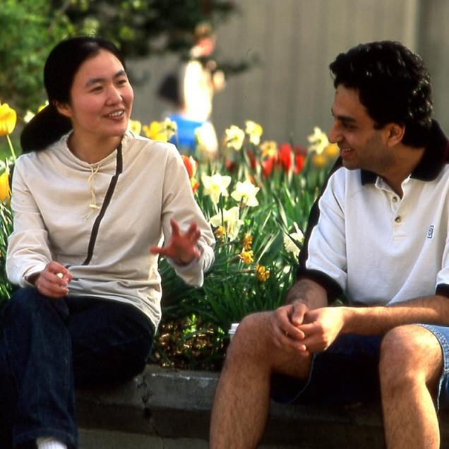 Rutgers Global – Summer Bridge Program in Social Work, a man and a woman converse outdoors near a flower bed