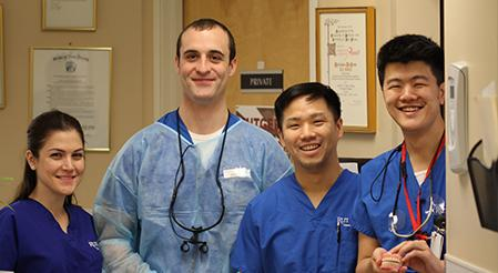 Rutgers Health - team of dental students and dentists pose holding dentures