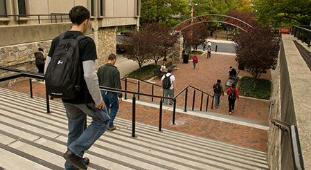 Rutgers Global - CLiME, student descends large set of steps outside on Rutgers-Newark campus