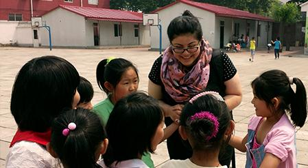Rutgers Global - Service-Learning Abroad, female Rutgers student talks to a group of children in a schoolyard in China