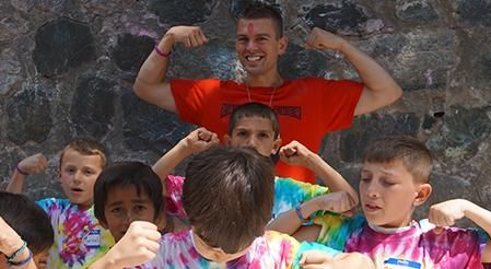Rutgers Global - Rutgers Staff Employ Peace Corps Tradition, a Peace Corps volunteer (left) plays with a group of local children wearing tye-dye tee shirts at a youth center in Albania