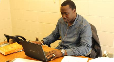Rutgers Global - Fulbright Scholar Saliou Dione, Saliou Dione sitting at desk typing on a laptop