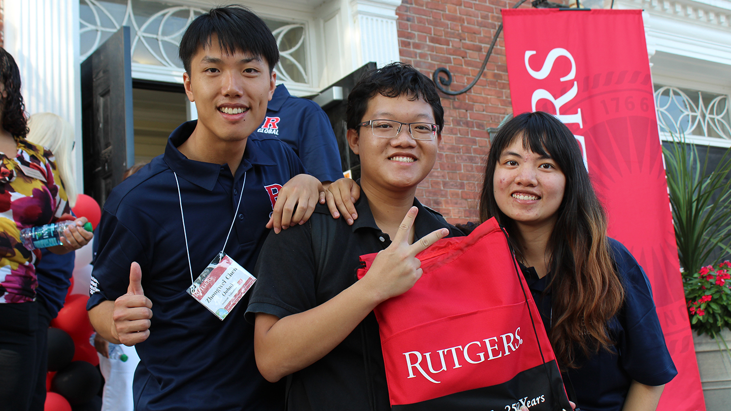 Rutgers Global - Services for International Students, three international students pose with Rutgers gear outside College Avenue gym