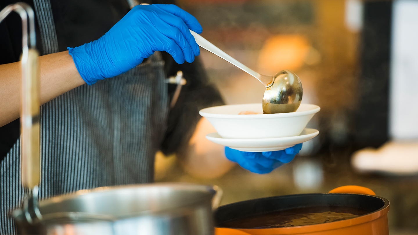 Rutgers Against Hunger - A gloved hand pours soup from a ladle into a bowl